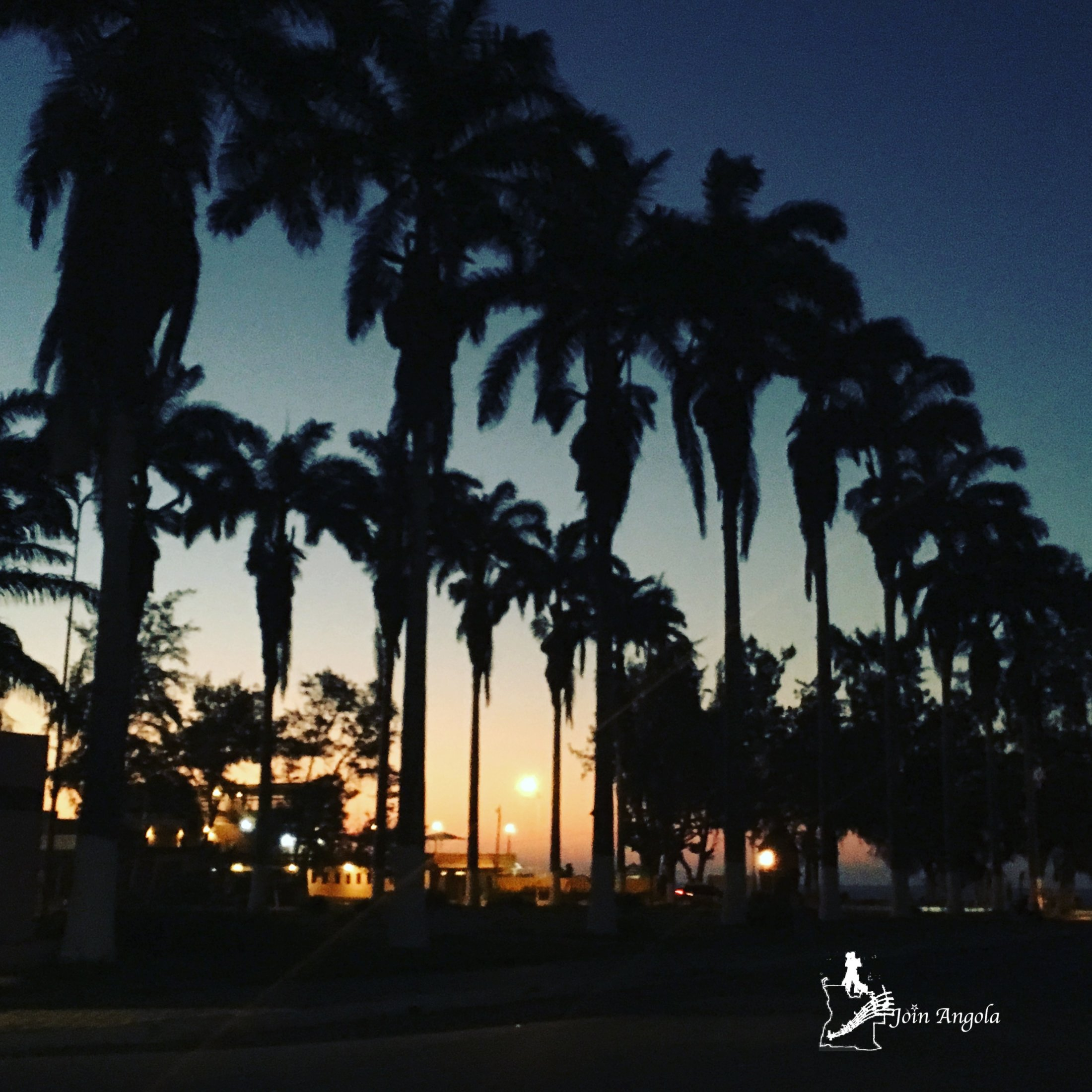 A beautiful sunset in the Largo da Feira, a space that is close to Praia Morena (the main beach in the city of Benguela) and filled with small bars and restaurants. The two rows of tall palms look particularly beautiful when the sun is setting over the sea behind them.